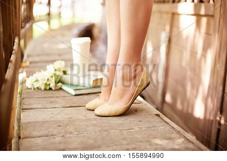 Legs of a girl standing on tiptoes on wooden balcony