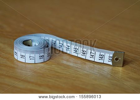 Tape measure (measuring length in centimeters and meters, frequently used for measuring the perimeter of human body during the diet) on the wooden surface