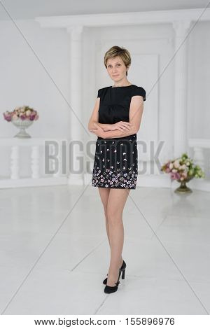 young woman with short hair in a black mini dress isolated on white background