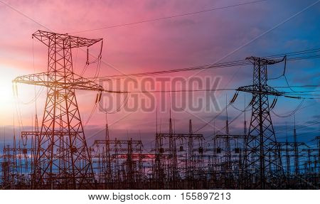 Electrical pylons on the background of the transformer substation during sunset