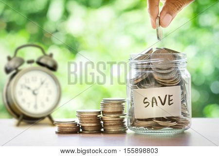 Hand putting Coins in glass jar time for money saving financial concept