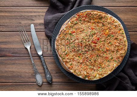 Lahmacun traditional turkish delicious armenian pizza with minced beef or lamb meat, paprika, tomatoes, cumin spice, parsley baked spicy middle eastern arabian food on rustic wooden table background
