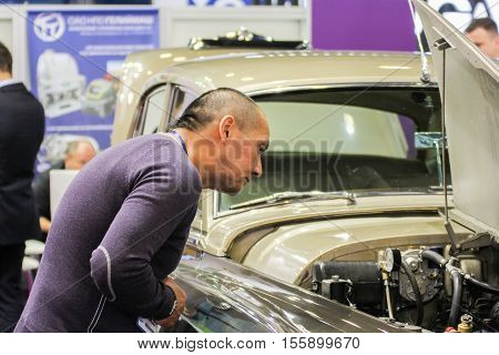 St. Petersburg, Russia - 4 October, A man looks into the engine compartment of cars, 4 October, 2016. Petersburg Gas Forum which takes place in Expoforum.