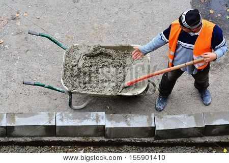 CLUJ-NAPOCA ROMANIA - SEPTEMBER 15 2016: Workers shovel wet concrete from wheelbarrow to fix the curb blocks. Road work curb installation