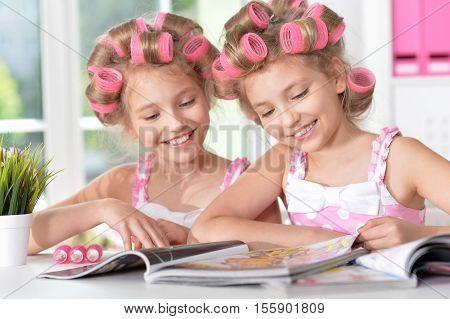 Cute  tweenie girls  in hair curlers  with magazine