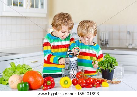 Two little kid boys making healthy salad with fresh vegetables in domestic kitchen. Siblings children in colorful shirts having fun with helping at home.
