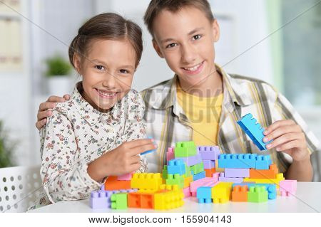 Portrait of bother and sister playing lego and looking at the camera