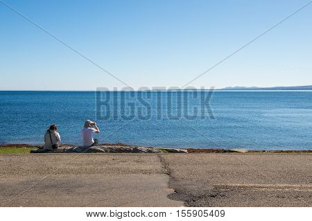 Gaspe Peninsula Quebec Canada - 29 September 2016: Back view of two tourists enjoying seascape in Forillon National Park.