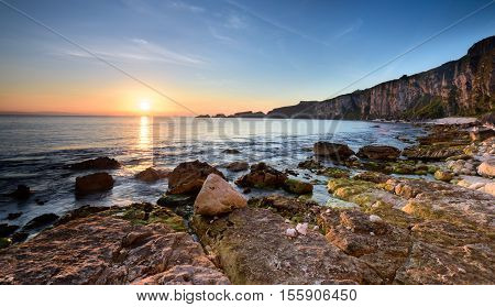 Dawn rises over the horizon and the Carrick-a-Rede archipelago as waves lap onto the limestone shore. Antrim Coast, Northern Ireland