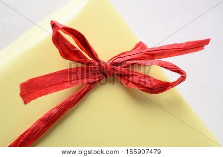 Red Raffia Bow On Yellow Gift Wrapped Package