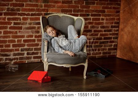 Cute little girl in soft pajamas reclines in a chair with a wistful look. She has retired to the empty room. Near a chair the half-open bright box with gift lies. On a background of a dark brick wall.