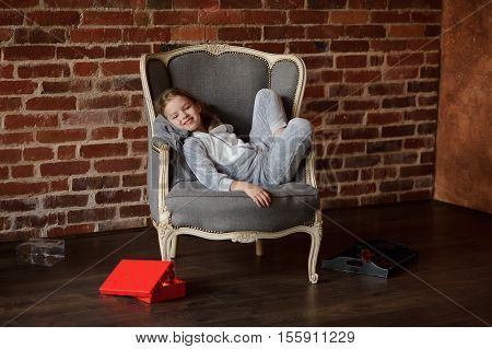 Little girl in soft gray pajamas reclines in chair with smile upon the face. She has retired to empty room. Near a chair the half-open bright box with gift lies. On a background of a dark brick wall.