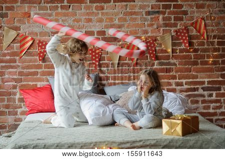 Christmas morning. Two children have put up a cheerful fight on a big bed. Brick wall is decorated with Christmas garlands. On the edge of a bed there is a Christmas gift. Children adore Christmas.