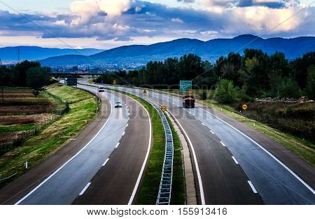 Open highway through pastoral landscape with light traffic
