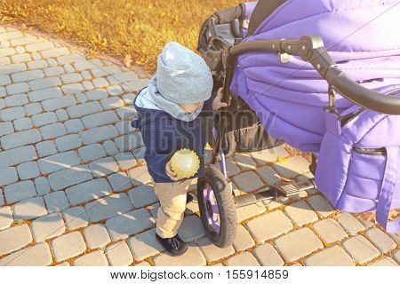 Cute baby playing with rubber ball near stroller in park
