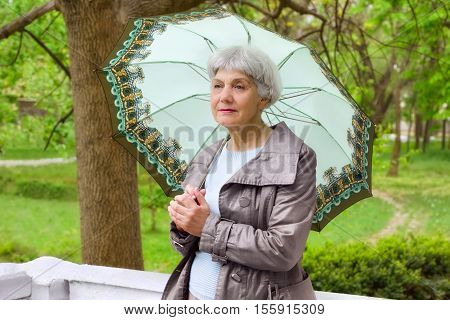 cute elderly woman senior with an umbrella on the beautiful white verandah in the park near the house