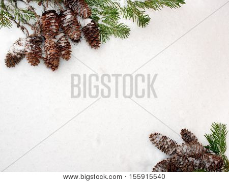 Christmas background. Green spruce branches and cones are located diagonally opposite each other on the white snow.