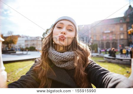 Girl in coat make selfie. send air kiss. in warm clothes