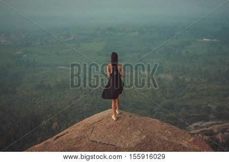 Women in black dress at the top of cliff on sunrise and green rice field