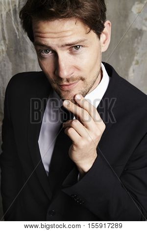 Smug businessman looking at camera studio shot