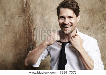 Handsome Businessman untying tie portrait studio shot