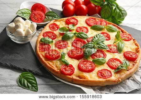 Fresh tasty pizza Margarita on slate plate, closeup