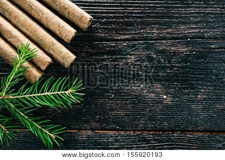 Group of cigars on the dark brown wooden surface. Flat lay. Selective focus