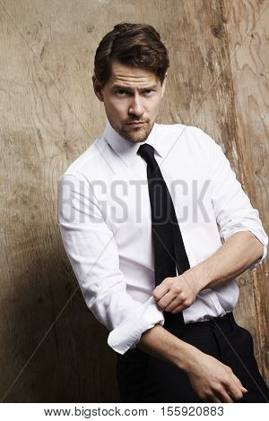 Handsome Businessman rolling up sleeves portrait studio