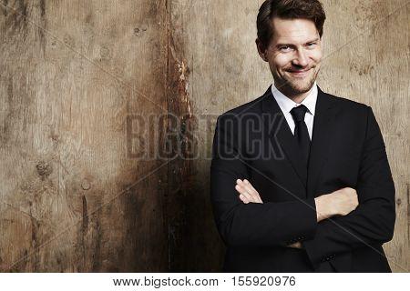 Confident wallstreet businessman smiling at camera studio