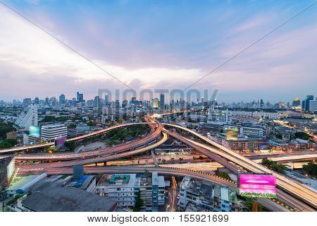 Sunset scene of Bangkok cityscape with blue sky and clouds. Traffic on the freeway in the business district. at dusk.Expressway and Highway top view.Twilight scene with traffic light Thailand.