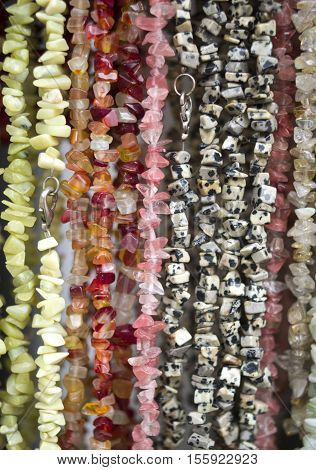 Many colorful necklaces of semiprecious stones in store