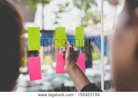 Young Businesswoman With Colleague Sticking Adhesive Notes On Glass Wall In Office