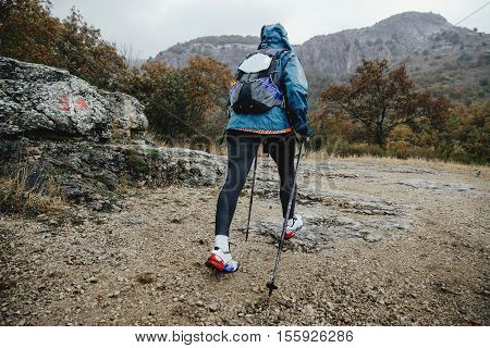 woman hikers with walking poles traveling in rainy weather on mountain trail
