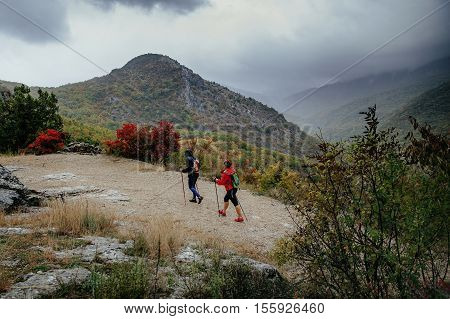 people hikers with walking poles travelling on a mountain trail in autumn rain