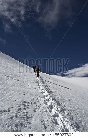 alpinists climbing allalinhorn in swiss alps during summer