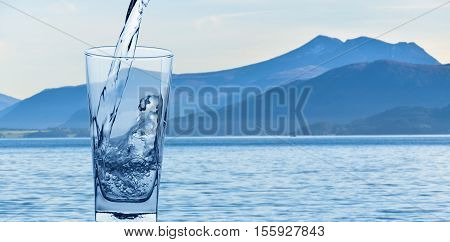glass with water on background of mountains and lakes
