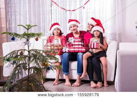 family, christmas, holidays and people concept - happy indian siblings with gift box sitting on sofa at home, four indian young siblings celebrating christmas, merry christmas