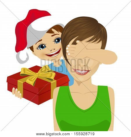 son wearing santa hat giving to mother christmas gift covering her eyes with his hand over white background