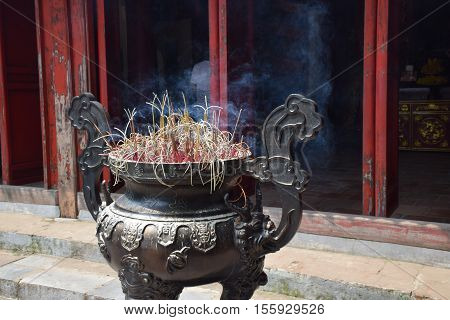 Incense sticks burning in a incense burner inside Den Quan Tranh temple in Hanoi, Vietnam