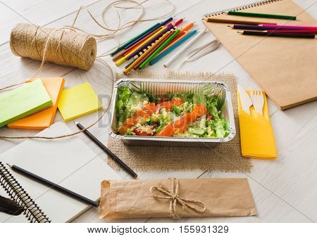 Healthy lunch of artist. Diet concept. Take away food in foil boxes, papers and pencils on working table of creative person or art student. Salmon salad on white wood