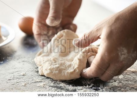 Male hands kneading fresh dough on table