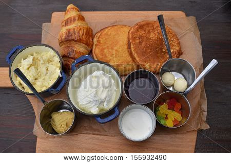 Breakfast with scrambled eggs pancakes croissant jam cottage cheese butter yogurt meat pate and sweetmeats served on cutting board over wooden table. Top view.