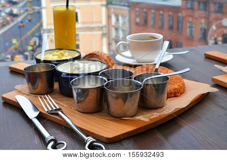 Breakfast with coffee orange juice scrambled eggs pancakes croissant jam cottage cheese butter yogurt meat pate and sweetmeats served on cutting board over wooden table. Top view.