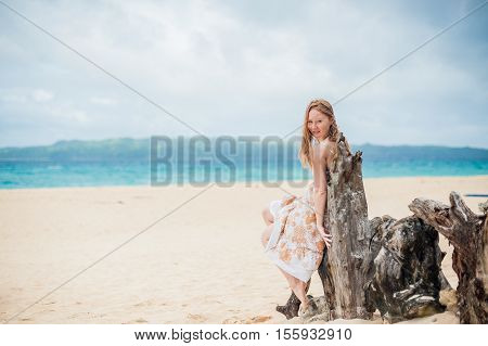 Young girl sitting on an old tree on the beach of Boracay Island