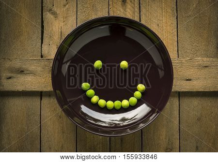 Smile face from lotus seed in drak brown dish on wood background