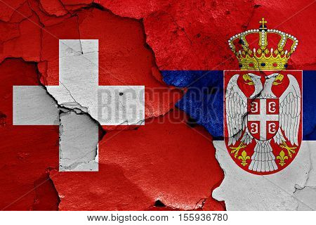 flags of Switzerland and Serbia painted on cracked wall