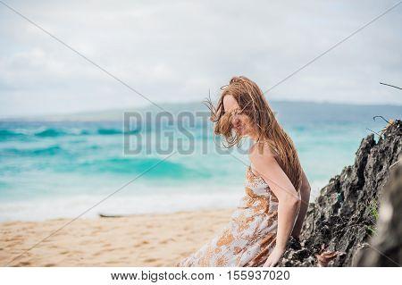 A Girl Sits On A Rock On The Beach Of Boracay