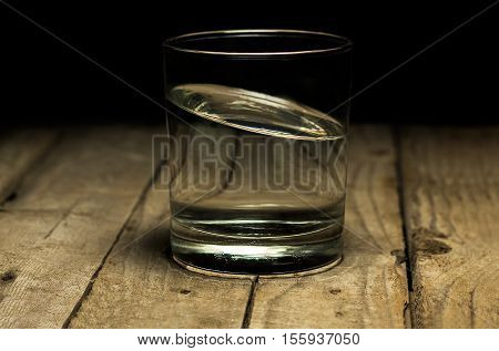 skew water in clear glass on wood table