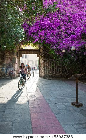 Kos Greece - May 14 2010 : Girls on bicycle under the main door of the medieval walls