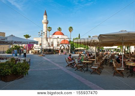 Kos Greece - May 14 2010 : The Defderdar Mosque in Eleftheria square with people sitting in the bars